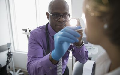 Male doctor examining mouth of female patient using tongue depressor and flashlight in clinic examination room