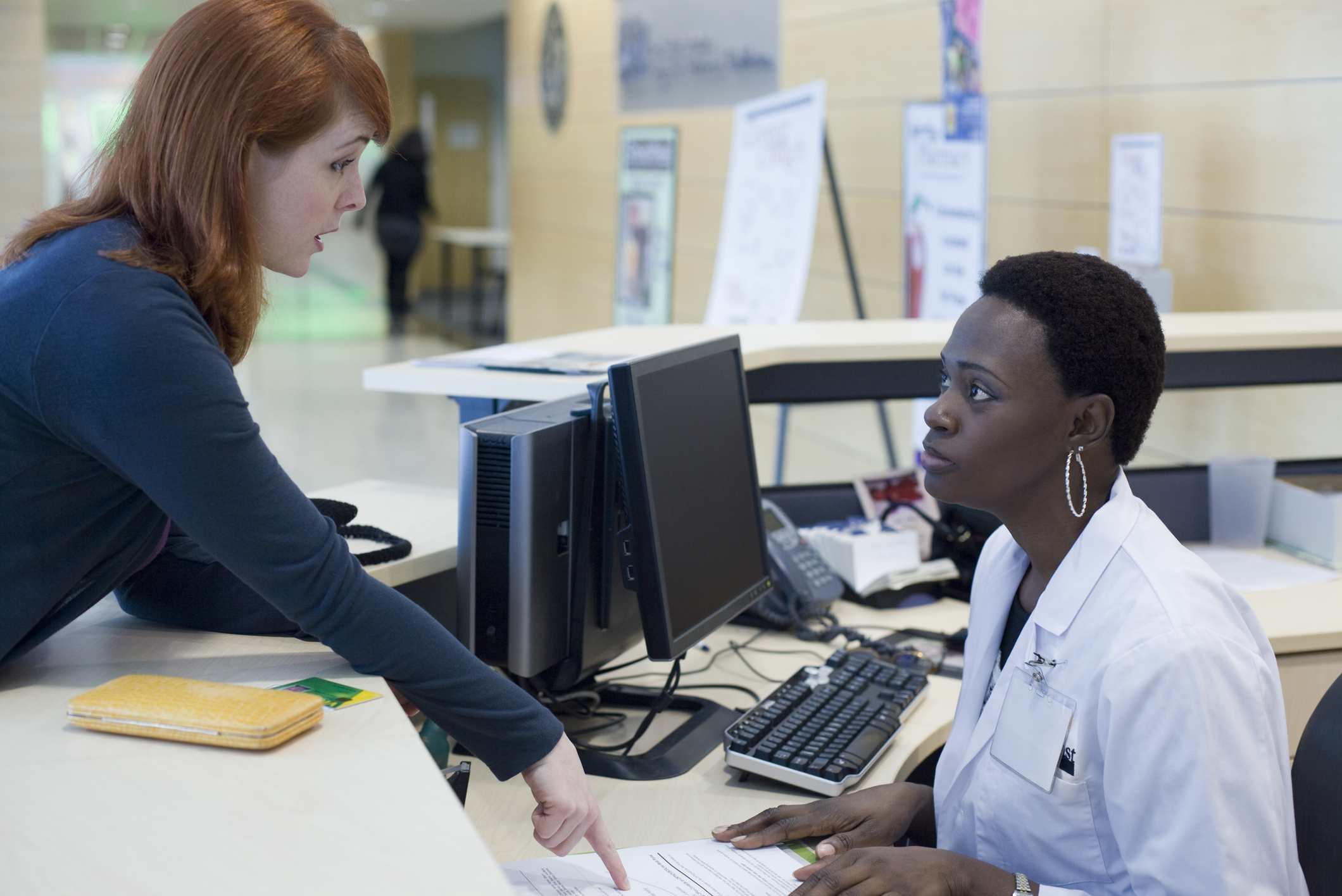 Upset patient explaining problem to medical receptionist