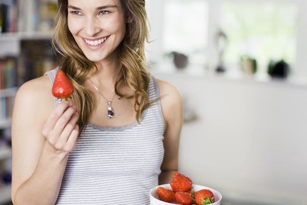 Woman eating a bowl of strawberries