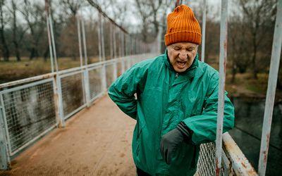 Senior man resting after jogging, he standing on a metal bridge