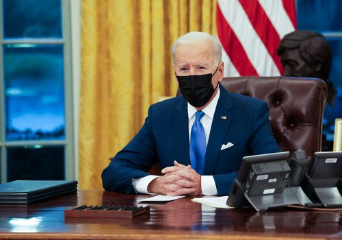 Joe Biden wearing a mask sitting in the oval office.