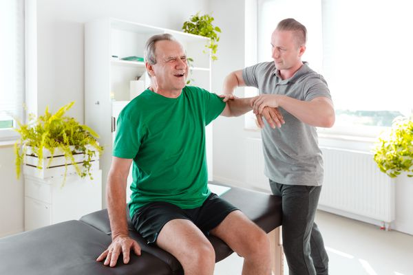 Photo of a senior man with shoulder pain being examined by a PT.