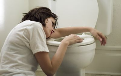 woman getting sick on toilet