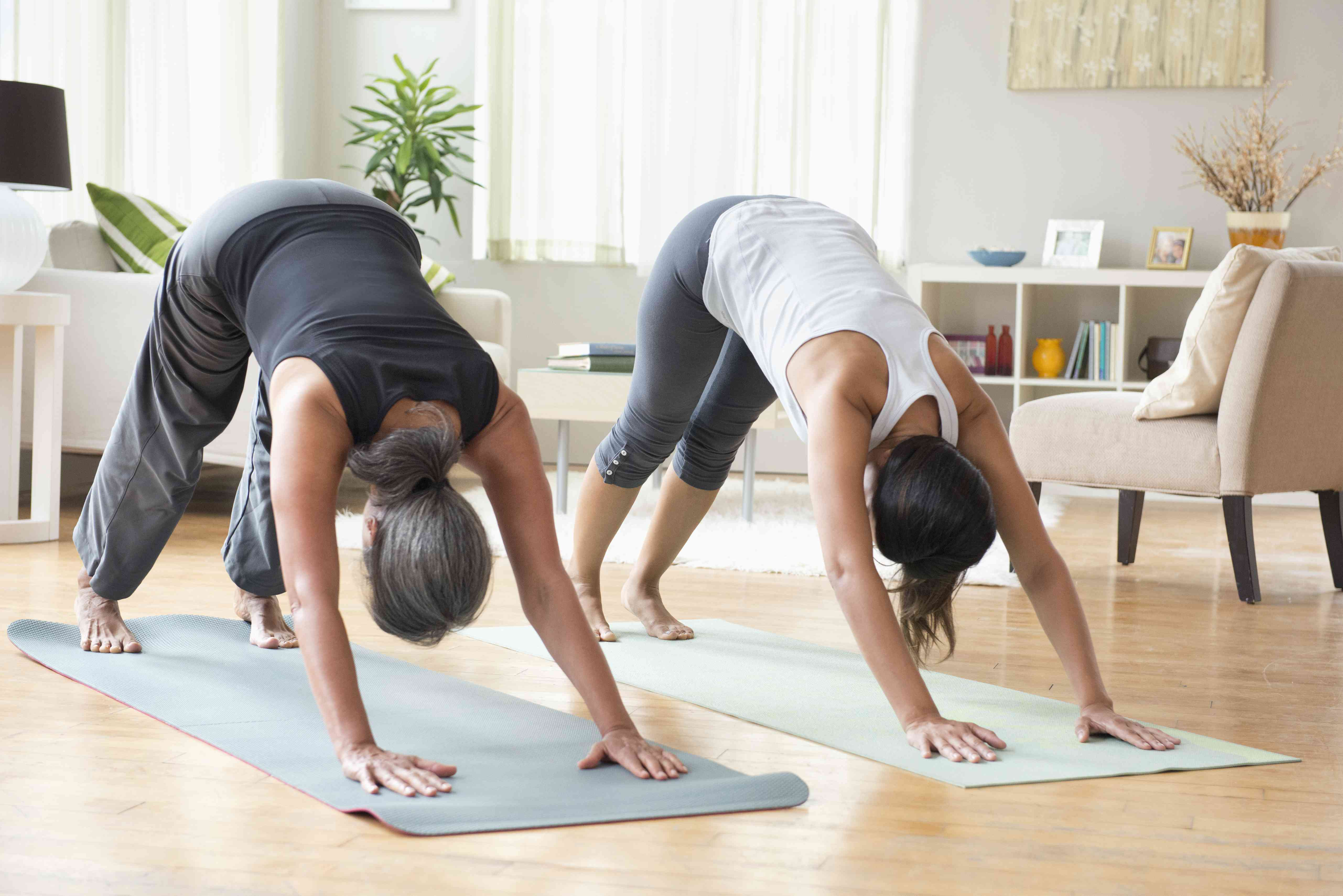 Mother and daughter performing yoga in livingroom