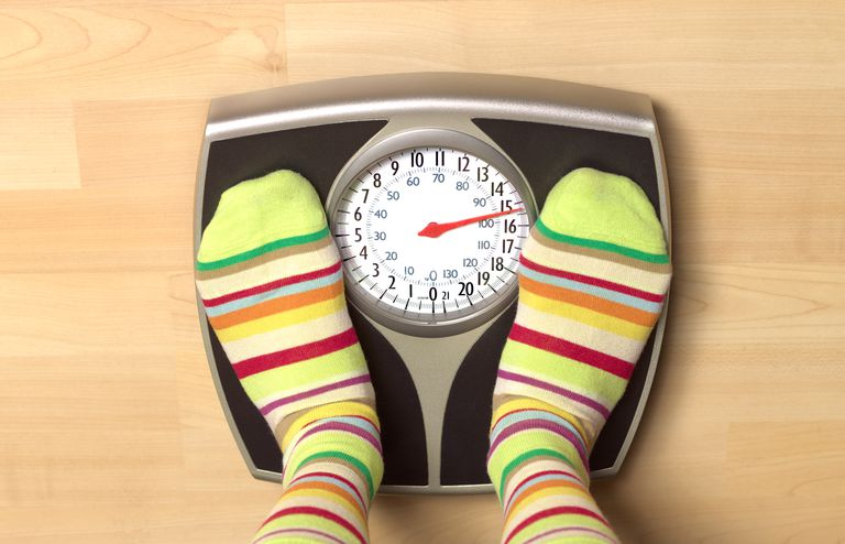 brightly colored socks of woman on bathroom scale