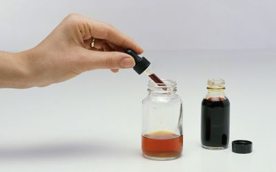 Hand with eye dropper and bottle of iodine