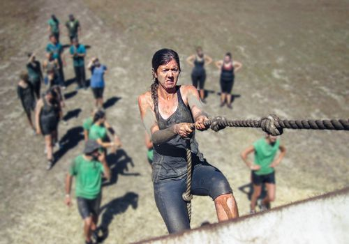 Woman using a knotted rope to climb a large wall Woman covered in mud using a knotted rope to climb a large wall as part of an obstacle course