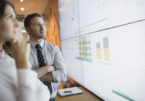 man and woman analyzing data on projected screen