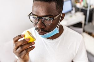 A young Black man with glasses has his mask down so that he can try to smell a lemon.