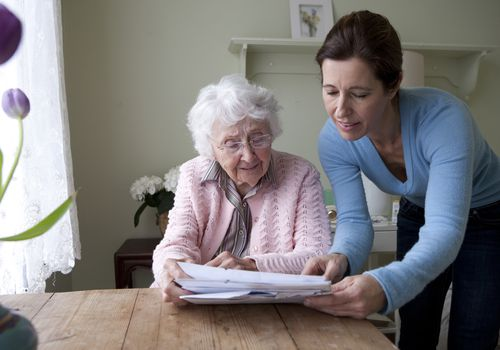 Caregiver and Senior Reading Together