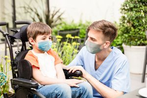 Child in wheelchair with nurse or therapist