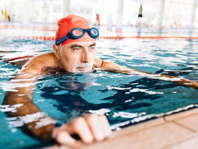 Senior man relaxing in water by edge of swimming pool