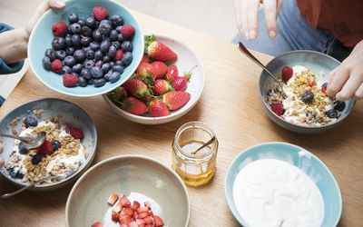 Table with bowls of berries and yogurt