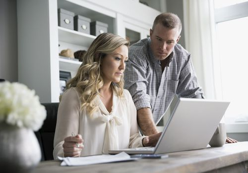 Couple working at a laptop in a home office