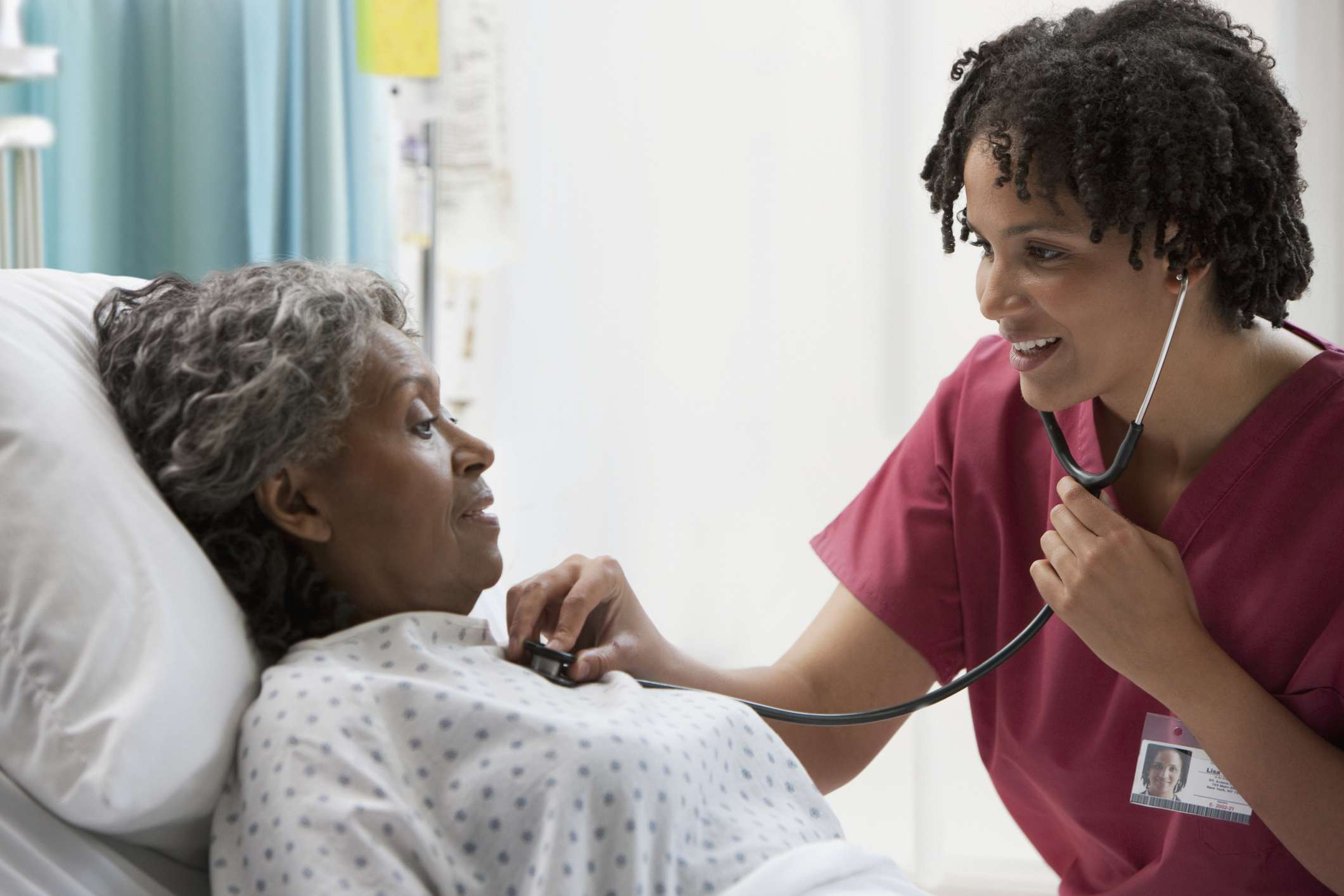 Nurse using stethoscope on hospital patient's chest and heart area