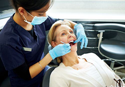 woman having her teeth checked by dentist