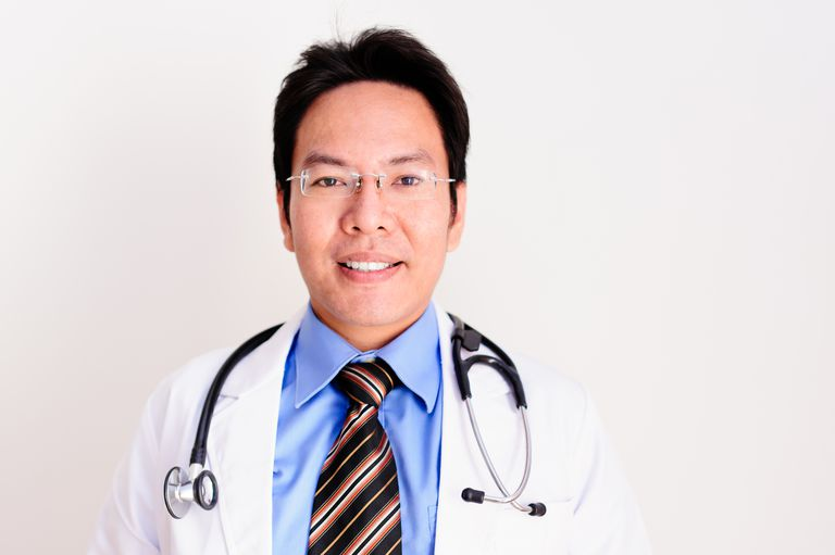 Male physician in white jacket with stethoscope around neck.