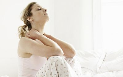 Portrait of woman stretching while sitting on bed