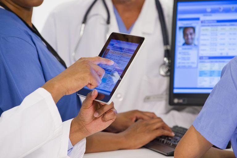 Doctors using digital tablet together in hospital - stock photo