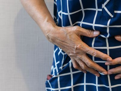 close up senior woman using hand to touch stomach after feeling pain