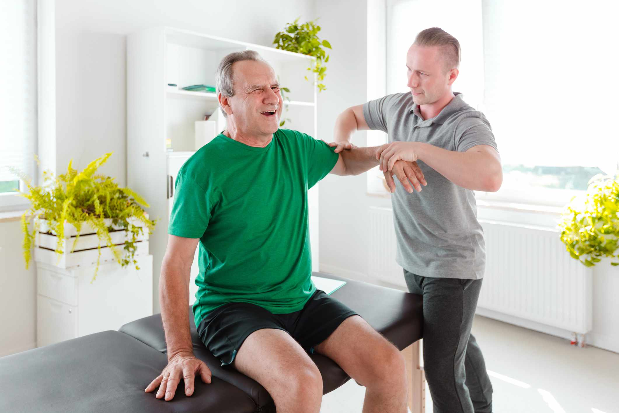 A man with shoulder pain being examined by his PT