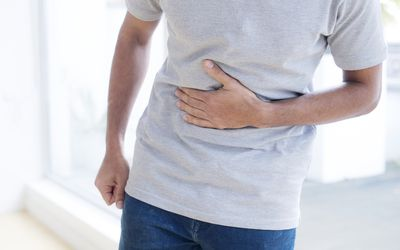 Man touching his stomach in pain