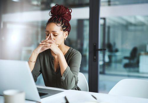 Black women feeling frustrated at work desk.