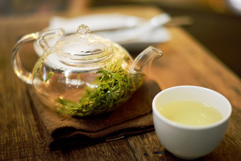 A glass teapot of green tea with a cup of green tea beside it.