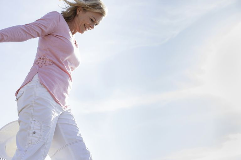 Low angle view of mature woman walking in breeze