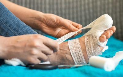 Woman bandaging her injured leg on sofa at home.