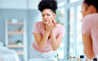Shot of a young woman with hands that look like she is popping a pimple.
