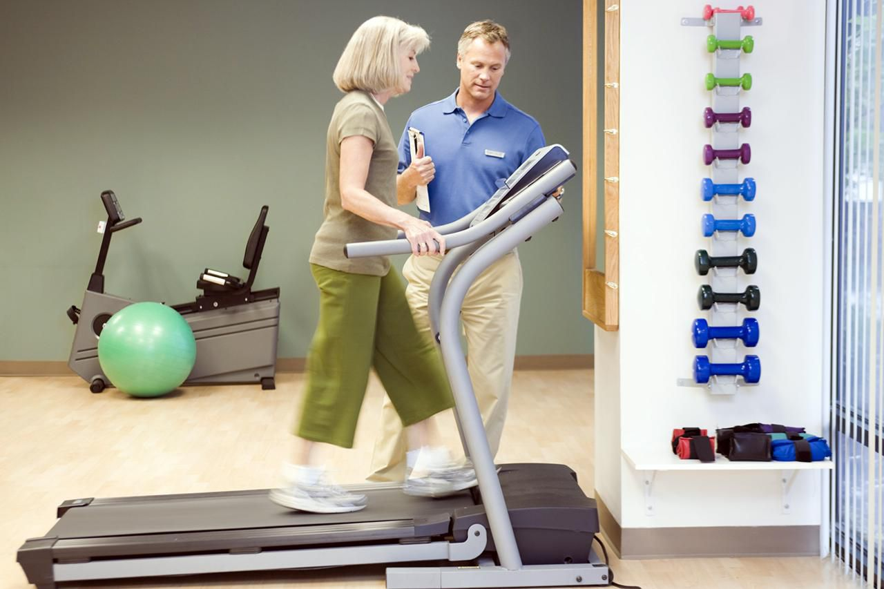 Physical trainer helping woman on treadmill