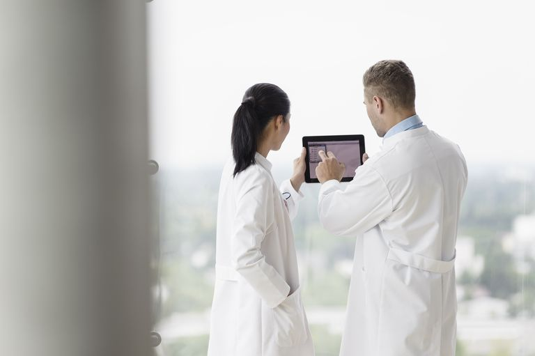 Doctors looking at a tablet