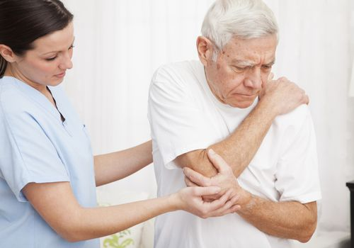 nurse helping older man with painful elbow