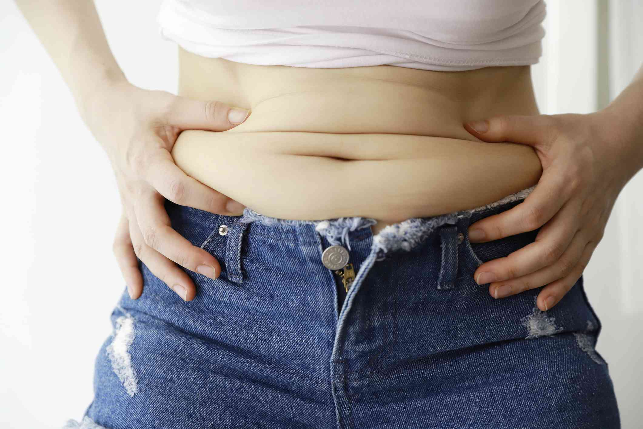Midsection Of Woman Holding Belly Fat