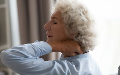 Older woman rubbing her neck