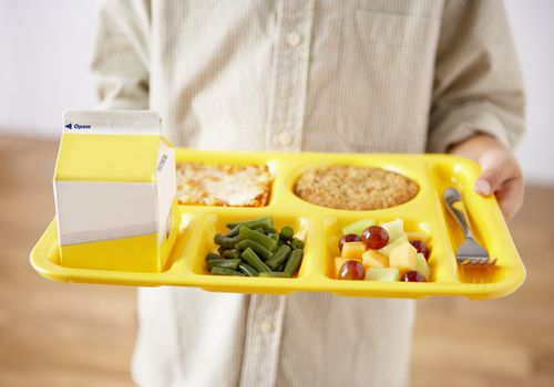 An unseen small child, probably a student, holding a bright yellow school lunch tray with yellow milk carton, green beans, mixed fruit, a slice of pizza, a dessert which is not in focus, and a fork.