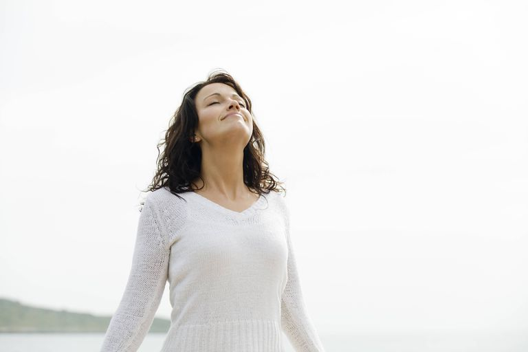 Smiling woman standing with her face turned towards the sun, soaking up light and fresh air