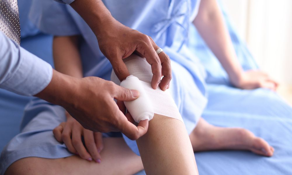 Close up hand of Doctor wrapping a bandage to the knee of patients
