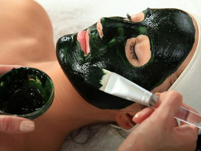 Woman having a clay mask applied to her face, during an acne treatment facial.