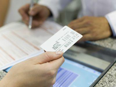 woman handing over helath insurance card