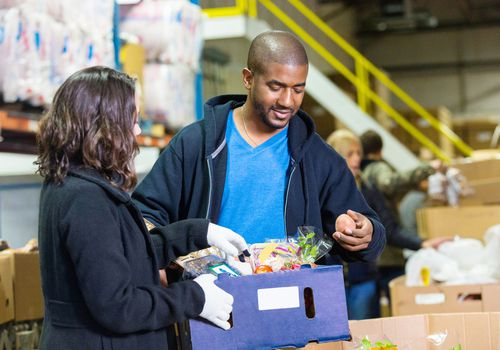 man and woman looking through box of food