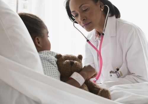 Doctor with stethoscope examining young girl in hospital bed
