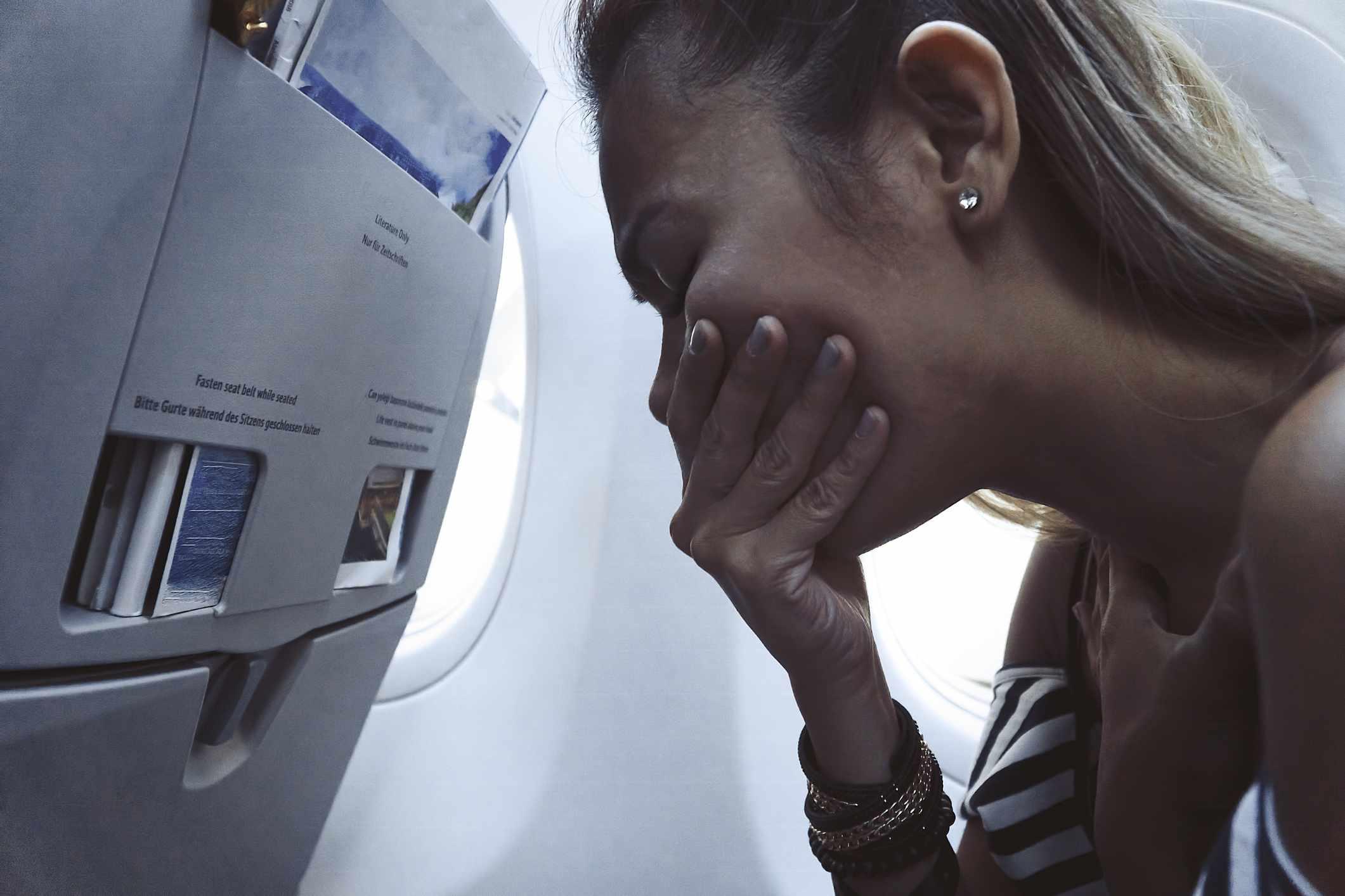 Woman on a plane feeling nauseous