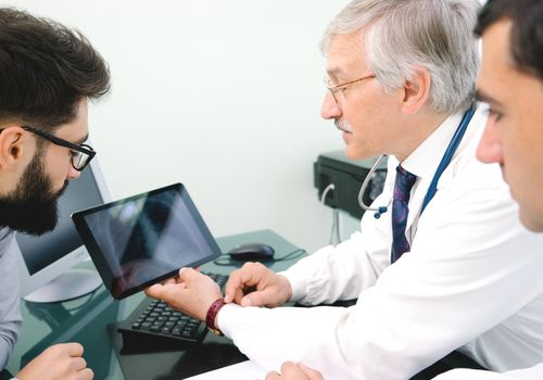 Male doctor talking to two men and and holding a tablet showing a chest x-ray