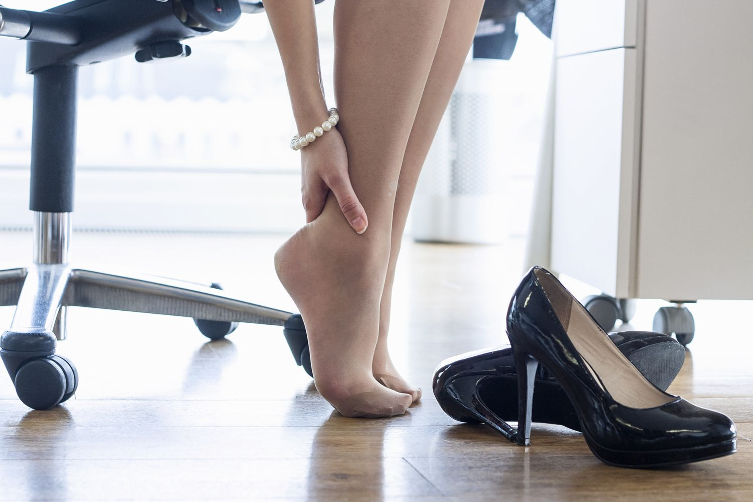 A woman with her heels off rubbing the back of her ankle