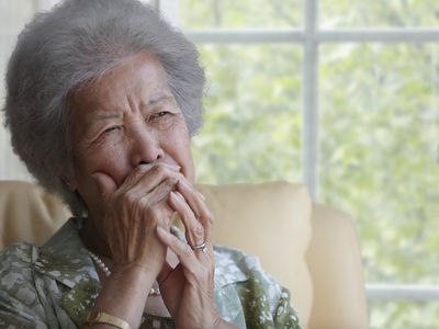 Senior woman covering her mouth with her hand