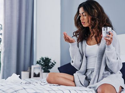 A woman with long brown hair sits on a bed, looking at the pill she is holding in one hand, while holding a glass of water in the other.