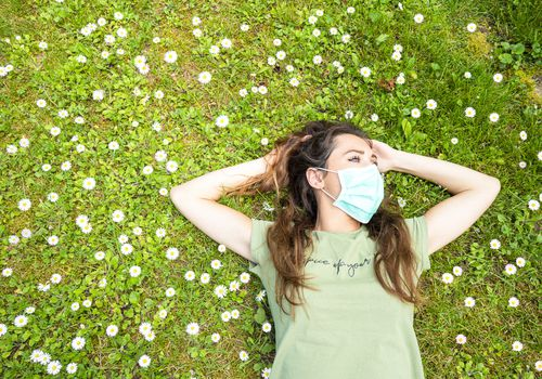 A young white woman with long hair laying on the grass surrounded by small white flowers. She is wearing a disposable blue face mask and a green tee shirt.