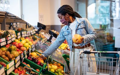 Woman shopping for fruits in grocery store.
